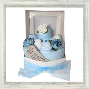 blue baby blanket, towels and clothes handcrafted to look like a cake.