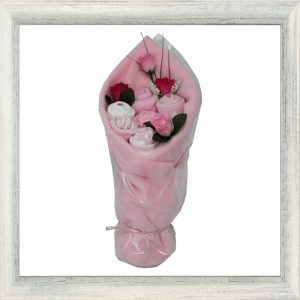 Pink cotton baby garments and blanket handcrafted into a bouquet of flowers.