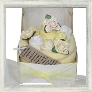 yellow celebration cake made from 100% cotton Long sleeve Sleepsuit 3-6 months, 100% cotton bodysuit 3-6 months, 100% cotton bib, 3 pairs of cotton rich socks all wrapped up in a supersoft fleece blanket and placed in a white box with a yellow ribbon bow.
