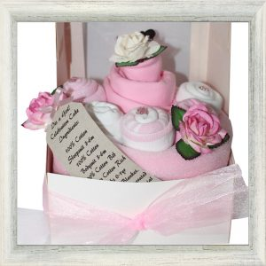 Pink themed 100% cotton Long sleeve Sleepsuit 3-6 months, 100% cotton bodysuit 3-6 months, 100% cotton bib, 3 pairs of cotton rich socks all wrapped in a supersoft fleece blanket to resemble a cake and placed in a white box with ribbon bow.